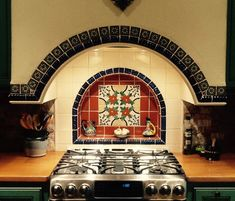 Elegant stove alcove bordered with Mexican tile, centered around a well-designed red backdrop.