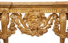 Detail of carving The Buxted Park Console Table  An important George II carved giltwood side table, attributed to Matthias Lock, the deeply fluted frieze with an upper leaf border issuing swags of finely carved leaves and flowers between scallop shells centred by a bearded classical mask depicting Jupiter adorned with acanthus decoration, on eight elaborately carved and scrolling cabriole legs terminating in claw and ball feet