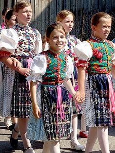 Girls in traditional dresses, called 'kroj' sing in a parade on St John's day. Taken in Jakubany, Slovakia.