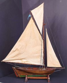 c.1900 - A handsome English pond yacht, handcrafted from wood and brass and featuring vintage cloth sails and fittings. Displayed on a separate, custom-fitted stand.