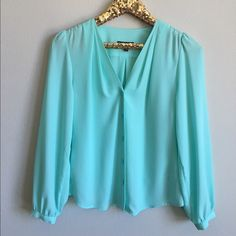 Express V-Neck Blouse Beautiful Tiffany blue colored blouse. Only worn once and it great condition. There is a very small mark on the top shoulder pictured above. The front has pleats coming from the top with a gathered shoulder. Button closure at wrist. Front is loose and flowy. Express Tops Blouses