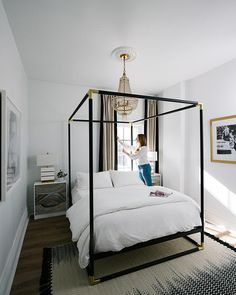 You need to see Havenly Head of Design Shelby Girard's black and white chic, modern home makeover—we love this big comfy statement canopy bed outfitted with plush white bedding and gorgeous chandelier above! Click to see more of this gorgeous renovation.