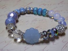 Made in Periwinkle Blues and silver beads. Gorgeous Czech Glass in an array of styles and Opalite moonstone beads accented with a silver pave bead. This bracelet is made on stretch with no clasp. Easy