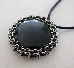 """This black onyx cabochon is extremely well-cut and polished. Black onyx has traditionally been used to banish grief and enhance self-control. Oxidized silver plated jump rings are woven so that they hold the coin firmly in place... and it turned out very nice, I think :) Although, it took an hour to """"battle"""" with slippery cabochon to squeeze it into the bezel :) Diameter of this pendant 1 3/4"""" (45mm)"""