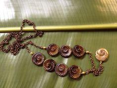 Nautilus é um colar de 40 cm de comprimento (incluindo o pingente de bronze) porém leve, de aspecto delicado e esportivo. Contém contas artesanais de cerâmica e termina em um pingente de bronze - modelado, esculpido e fundido - artesanalmente.
