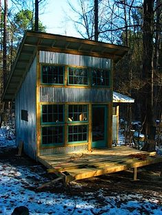 Two story tiny house with  corrugated galvanized siding and green painted windows.  ....I would LOVE to have a little place like this somewhere in the woods one day!
