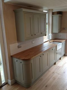 Sage green kitchen (Benchmarx range) with treated oak work surface and Belfast sink. Victorian tiles laid in a brick bond make for a stunning classic look.:
