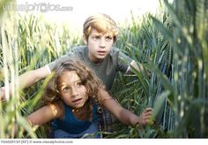 Girl and boy hiding in a wheat field