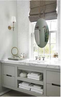 Grey bathroom with floating mirror in front of window
