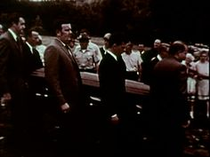 Pallbearers carrying the coffin of Mary Jo Kopechne; Senator EDWARD KENNEDY wearing neck brace, trailing casket; Ted Kennedy walking through crowd wearing neck brace. Chappaquiddick affair on January...