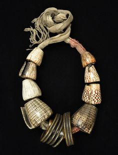 """Akusan (woman's belt)  Bontoc, Philippines  Conus shells, coiled brass, woven cotton fabric, human bone  35"""" (89 cm) long, as tied, largest conus shell is 2-1/2"""" (6.5 cm) long  Early 20th century"""