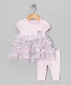 Feed a little sweetie's need for fabulous frills with this enchanting duo. Fitted with rows and rows of lacy ruffles, shimmering sequins and snaps in the back, it's perfectly primed for photo ops and fancy family gatherings. Includes top and leggingsTop body and leggings: 93% cotton / 7% spandexTop contrast: 100% polyesterMachine wash; tumble dryImported