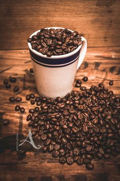 Old style fine art photo of a cafeteria cup holding brown coffee beans on old wooden advertising. Retro snack bar | Stock Photo - http://www.artstock.photos