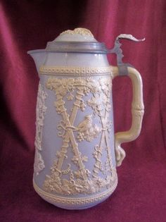 Gorgeous detailed Villeroy and Boch Mettlach 3 litre Stein with a grey/blue body and embossed cream colored grape vine design on the sides and top. This design is around an off white embossed design of a musician in a grape arbor with a German verse below. Pewter mounting for the lid.  Marked on the bottom in dark green with what looks like an angel with wings at the top, a banner reading Villeroy and Boch, and Mettlach in an arch below. Impressed with the number 1821.