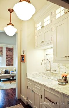 White kitchen with carrera marble and vintage pendant lights