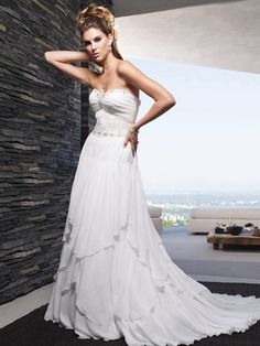 Style B007 features a beaded sweetheart neckline and bodice. The a-line silhouette is accented with soft tiers of silky chiffon. Available in White or Ivory.