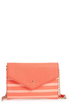 This coral Kate Spade bag flawlessly transitions from a graphic crossbody during the day to a chic and polished clutch by night.
