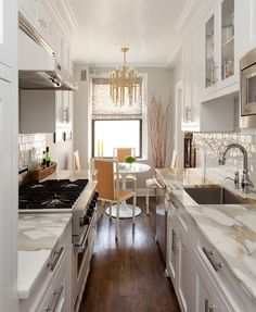 Small galley kitchen in NY apartment done very well. Saarinen Dining Table, Jonathan Adler brass chandelier, marble counters, 3x6 subway tile with orangy-brown grout.