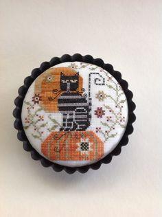 "Cross stitched black cat  in tart pan "" Olga"" by Plum Street Samplers."