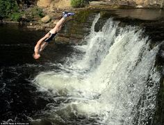 Risky business: As the heatwave rises to new levels across the country, a young swimmer in Richmond, North Yorkshire, England cools off by diving from waterfalls into the cooling waters of the River Swale yesterday