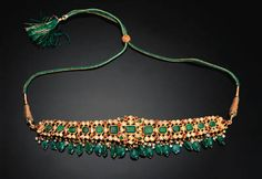 AN EMERALD, RUBY AND DIAMOND SET GOLD NECKLACE (GULUBAND) INDIA, 19TH CENTURY Composed of square-cut emeralds surrounded by smaller diamonds and rubies, the reverse with fine enamel floral decoration in red, white, green and blue, small uncut emeralds and pearls suspended below, slight chipping to enamel, condition generally good 8in. (20.3cm.) long