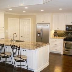 White cabinets, dark wood floors, tan granite