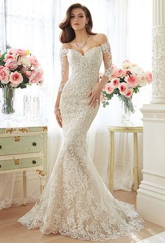 Brides: Sophia Tolli. Off-the-shoulder lace and misty tulle trumpet gown with sheer lace three-quarter length sleeves. Sweetheart bodice with lightly hand-beaded lace appliqués placed in a shadowbox method. Semi-sheer lace back bodice and back zipper both trimmed with diamante buttons. Scalloped lace hem and chapel length train.