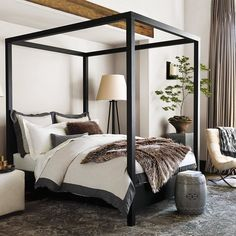 This modern canopy bed brings architectural drama to a bedroom, creating a room within a room! Shop the ebony-stained, hand-built oak beauty directly through the link in our profile.
