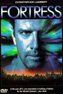 """Fortress""  A futuristic prison movie. Protagonist and wife are nabbed at a future US emigration point with an illegal baby during population control. The resulting prison experience is the subject of the movie. The prison is a futuristic one run by a private corporation bent on mind control in various ways."