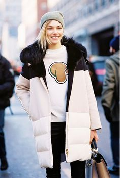 Jessica Hart in a down fur-hooded winter coat and beanie.