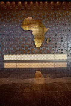 Geometric metal and wood wallcoverings shower the wall behind the African continent at the reception desk at the Sipopo Congress Center by Tabanlioglu Architects