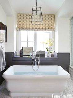 The Michelangelo soaking tub from Hydro Systems takes center stage in the master bath of a comfortable bachelor pad in Southern California.