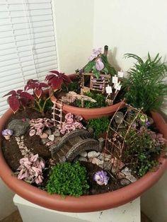 Jardin miniature zen créé dans des pots en terre cuite.
