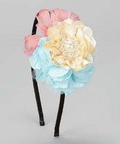 A bouquet of wispy feathers, satin petals and pearls creates a beautiful medley of textures that will surely dress tresses in captivating charm. Set atop a ribbon-lined band, this sweet treat smoothly slides on for an ouch-free fit.