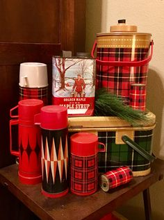 Vintage plaid thermoses with antique syrup tin decor on top of 1950's plaid metal picnic basket - love all things vintage!