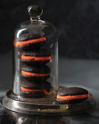 Halloween Whoopie Pies | Tender chocolate cake with a luscious creamy filling is great in any form, but it's most fun of all in a whoopie pie. These little cakes are dressed in their Halloween finest with orange sashes made by rolling the creamy edges in bright orange nonpareils.