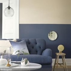 Die dunkelblaue Wandfarbe ziert lediglich den unteren Abschnitt der Wand. Darüber ist die Wandfarbe Beige. Beige und Blau ziehen sich durchs komplette Wohnzimmer…