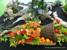 This vibrant arrangement of fruit and flowers was created by Linda Brown. This lovely arrangement formed part of a larger exhibit, created by the Aldershot Floral Design Club, for the RHS Hampton Court Palace Flower Show 2017.  This attractive arrangement includes roses, gerbera, lilies, ferns, chillies, oranges and apples.  This lovely photograph was taken by Janet Arm. Rhs Hampton Court, Fruit Arrangements, Flower Show, Gerbera, How To Make Notes, Cut Flowers, Lilies, Ferns, Exhibit