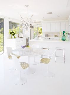 White kitchen and dining space with modern furniture and a Sputnik chandelier