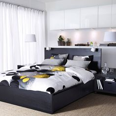 A bedroom with a black-brown MALM bed, BESTÅ storage with white doors and BOLLTISTEL quilt cover.