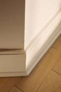 A finished edge on a laminate floor using quarter round trim at the bottom of the baseboards.
