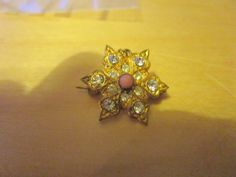 """vintage tiny thin brooch star shaped 12 clear stones/coral centre 3/4""""across"""