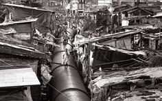 A PIPELINE carrying drinking water to more prosperous districts of India's largest city, Mumbai (population 20 million), passes through the shantytown of Mahim, where it serves as an impromptu thoroughfare. © Sebastião Salgado.