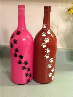 Wine bottles painted from inside out. Paws painted on outside of bottle. By AnnMarie Noreika