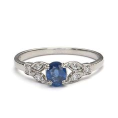 A lovely oval sapphire weighing 0.45 cts is set in a four prong basket with two diamond centered leaves on each shoulder and one at the top of the band (total weight 0.06 cts). This is a replica of an original circa 1930s engagement ring. Platinum. Size 5.5.