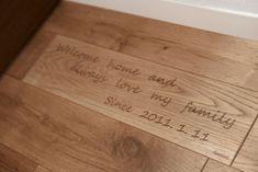 床には北海道産のナラの無垢材を使用。玄関を入った先には記念のプレートがある