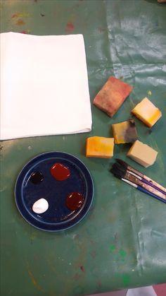 Käytimme vanhoja lautasliinoja kankaina kun aloimme toeuttamaan kankaan painantaa, jossa inspiraationa toimi jokin interventiotilamme pinta. Tähän otimme avuksi superlonin palasia ja siveltimiä. Maali oli valmiiksi sekotettua kuultopastaa.