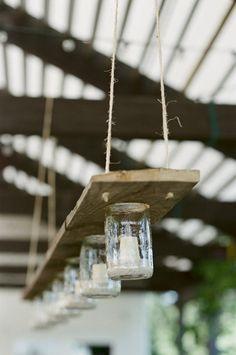 lumières de jardin fabriquées à la main sur une planche en bois avec de la ficelle, des pots de yaourts en verres et des bougies