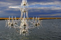 Bringing a huge glass and silver chandelier to the Venetian lagoon. At the sunset, it is so beautiful, and shining. Could you live without it? #chandelier #venice #design #architecture #murano #glass #andromedamurano