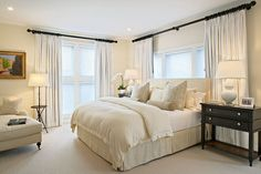 Beautiful serene room with White Curtains, bed linen, lamp , carpet and chair add a   Dark Wood side table .